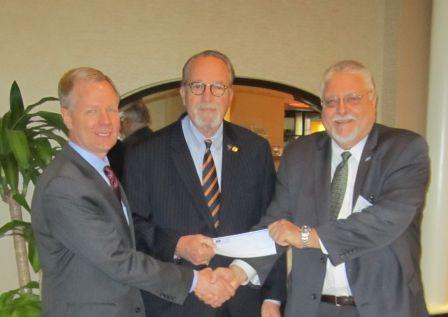 IACP President Chief Craig Steckler, center, accepts the donation from IJIS Institute Executive Director Steve Ambrosini, right. Shaking hands with Ambrosini is Bart Johnson, executive director, IACP, left.
